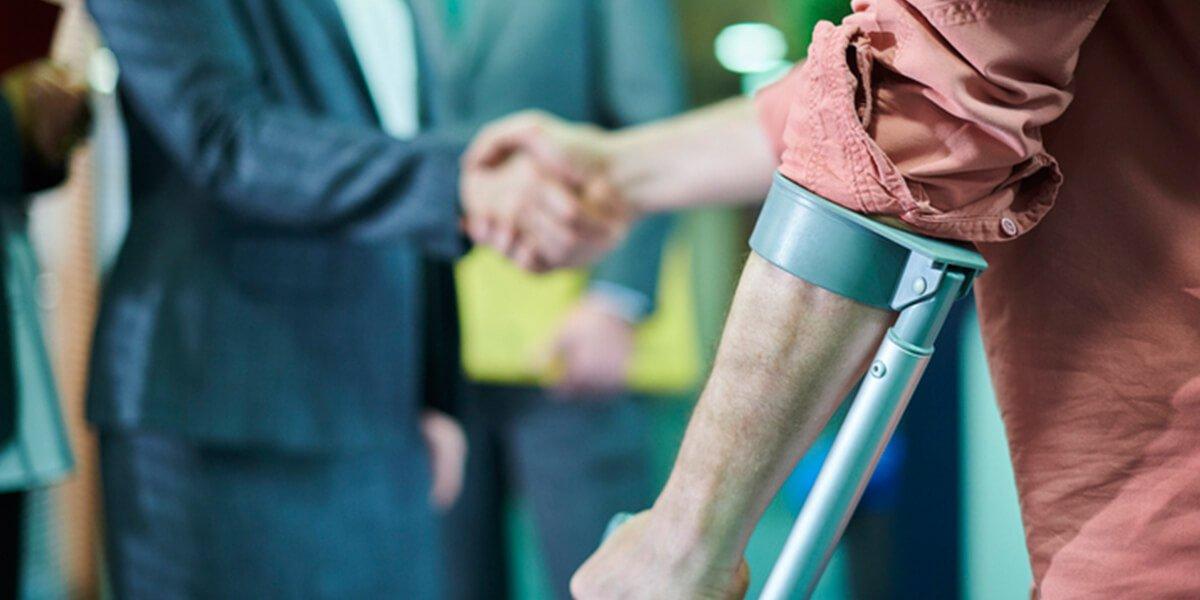 man on crutches shaking agent hand - insurance settlements - insurance planning farmington ct