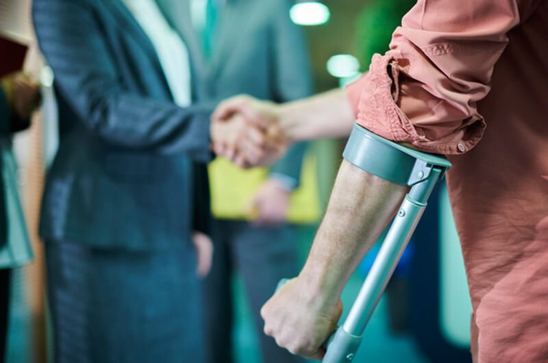 man on crutches shaking agent hand - insurance settlements - insurance planning farmington ct