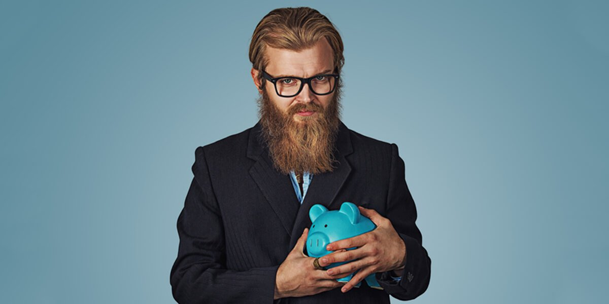young stingy man with piggy bank - be frugal not cheap - financial planning services farmington