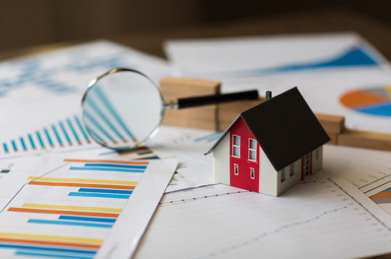 miniature home on financial graph - why house is bad investment - financial planning farmington
