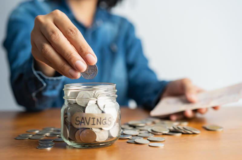 woman hand puts coins in jar - top tips for saving on a limited budget planning services farmington