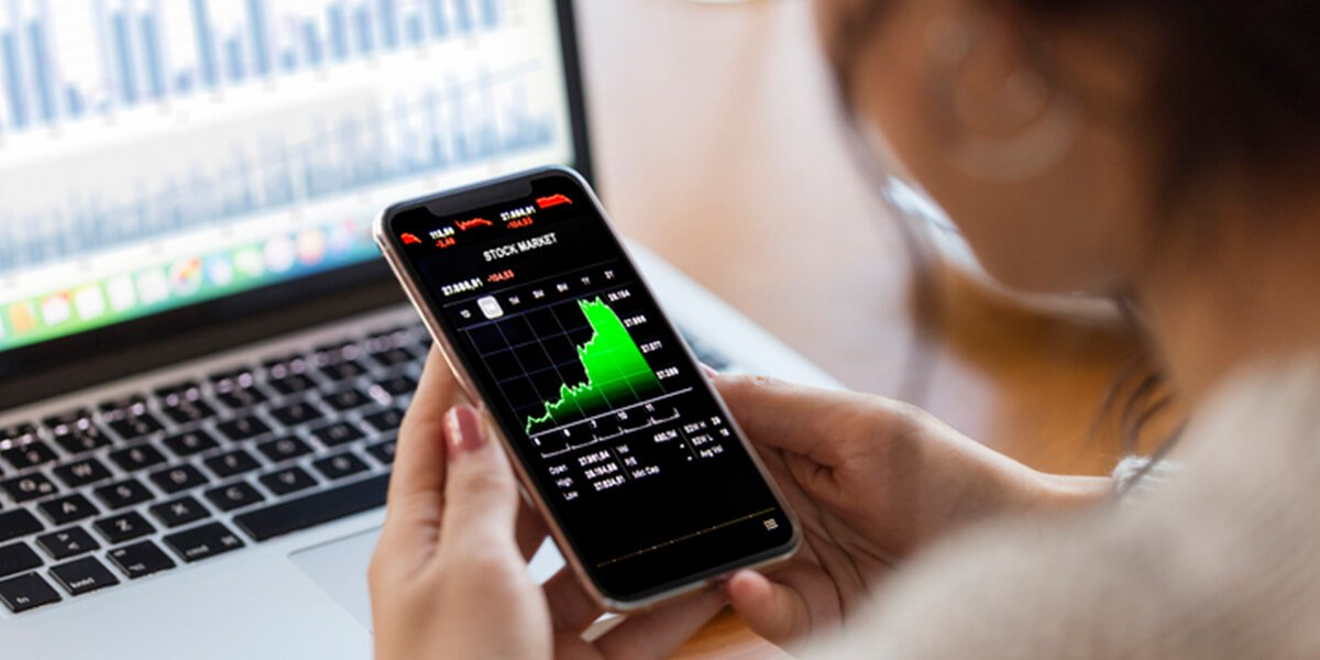 woman looking stock chart on phone - we provide investment planning services farmington ct